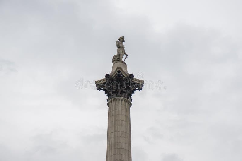 Κορυφή της στήλης του Nelson ` s στη πλατεία Τραφάλγκαρ, Λονδίνο ενάντια σε έναν γκρίζο συννεφιάζω ουρανό στοκ φωτογραφίες
