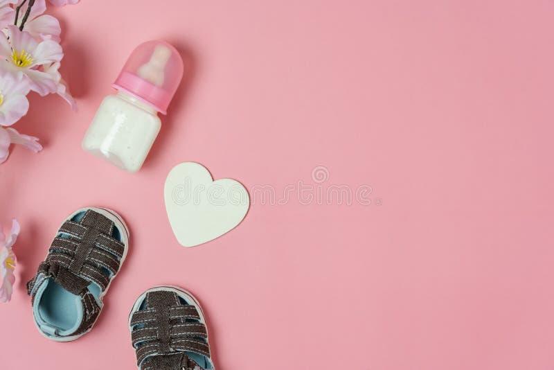 Κορυφαία εικόνα της διακόσμησης Χαρούμενες μητέρες, έννοια εορτασμού Μπουκάλι γάλα με μωρουδίστικα παπούτσια και αγάπη στοκ φωτογραφία με δικαίωμα ελεύθερης χρήσης