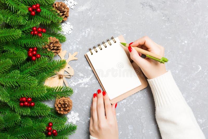 Κορυφαία θέα γυναικείου χεριού που γράφει σε ένα σημειωματάριο με τσιμέντο Χριστουγεννιάτικο φόντο δέντρο και εορταστικές διακοσμ στοκ εικόνα