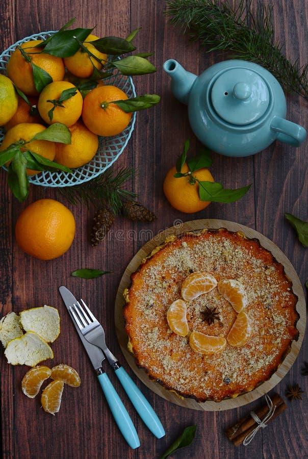 Κορυφαία θέα σε εσπεριδοειδή, tangerines σε μπλε καλάθια, τσαγιέρα, κωνοφόρο, πιρούνι και μαχαίρι σε ένα ξύλινο τραπέζι στοκ εικόνες