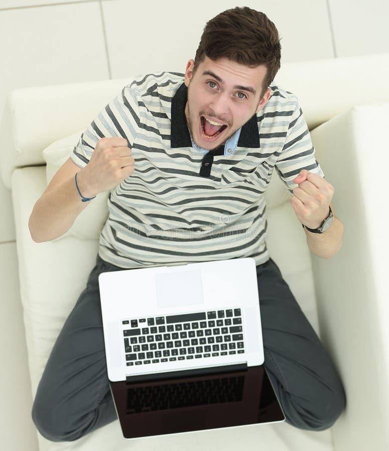 κορυφαία όψη χαρούμενος νεαρός άνδρας με τη συνεδρίαση lap-top στον καναπέ στοκ εικόνες