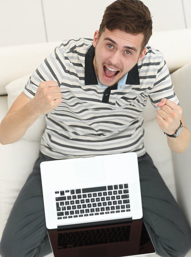 κορυφαία όψη χαρούμενος νεαρός άνδρας με τη συνεδρίαση lap-top στον καναπέ στοκ φωτογραφία με δικαίωμα ελεύθερης χρήσης