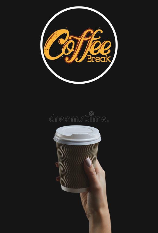 Κορόιδο γυναικείου χεριού που κρατά ένα φλιτζάνι καφέ σε σκούρο φόντο στοκ εικόνες με δικαίωμα ελεύθερης χρήσης