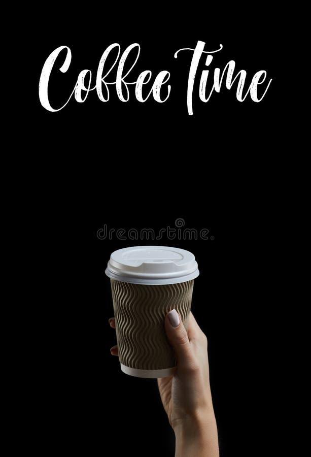 Κορόιδο γυναικείου χεριού που κρατά ένα φλιτζάνι καφέ σε σκούρο φόντο στοκ φωτογραφία