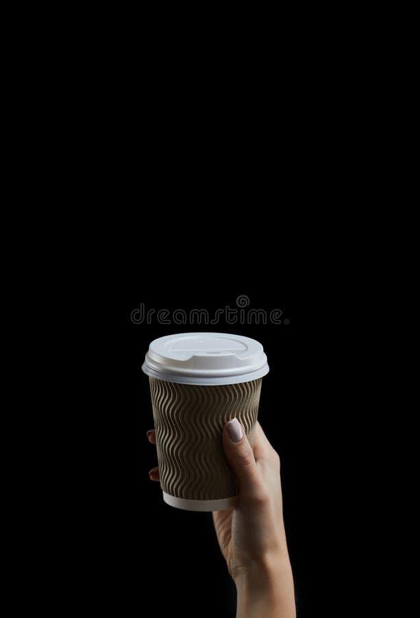 Κορόιδο γυναικείου χεριού που κρατά ένα φλιτζάνι καφέ σε σκούρο φόντο στοκ φωτογραφίες
