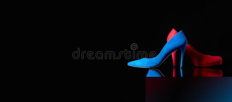 Κοτλέ παπούτσια των μπλε και κόκκινων γυναικών σε ένα μαύρο υπόβαθρο στοκ εικόνα με δικαίωμα ελεύθερης χρήσης