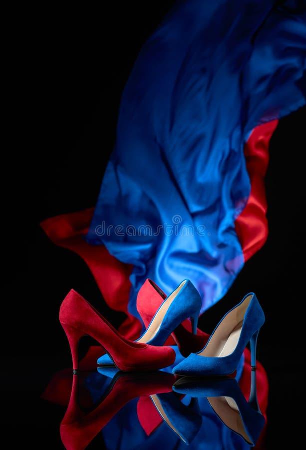 Κοτλέ παπούτσια των μπλε και κόκκινων γυναικών σε ένα μαύρο αντανακλαστικό υπόβαθρο στοκ φωτογραφίες με δικαίωμα ελεύθερης χρήσης