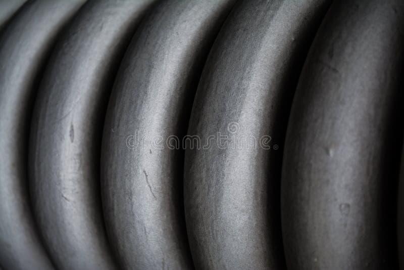 Κοτσίδα, σπείρα γκρίζα πυκνά από το μέταλλο, για τη συντήρηση των στοιχείων κατασκευής o Σύσταση ή ένα υπόβαθρο στους μονοφωνικού στοκ φωτογραφία