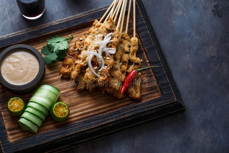 Κοτόπουλο Satay ή Sate Ayam - μαλαισιανά διάσημα τρόφιμα Είναι ένα πιάτο του καρυκευμένου, σουβλισμένου και ψημένου στη σχάρα κρέ στοκ εικόνα