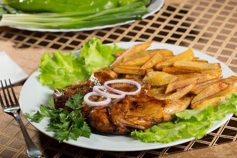 Κοτόπουλα καπνών με τις τηγανισμένες πατάτες στοκ εικόνες
