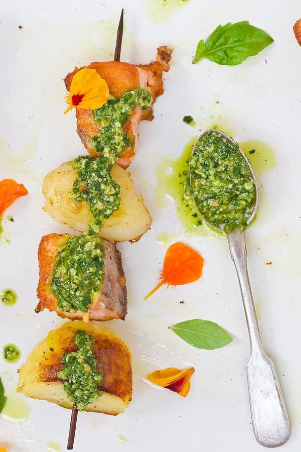 Κοτόπουλο και πατάτες σε ένα οβελίδιο με την πράσινη σάλτσα στοκ φωτογραφίες