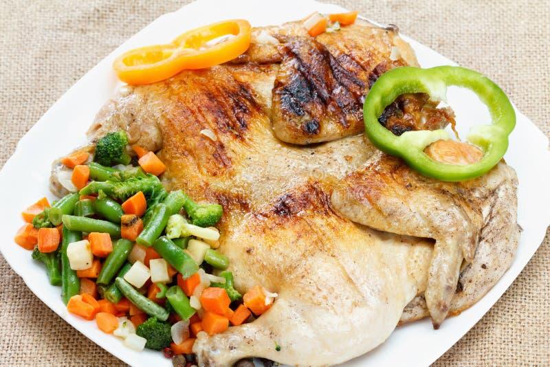 Κοτόπουλο που τηγανίζεται με τα λαχανικά σε μια πετσέτα burlap στοκ εικόνες