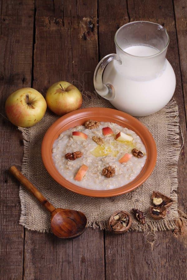 Κουάκερ με το γάλα, τα καρύδια και τα μήλα στοκ φωτογραφία