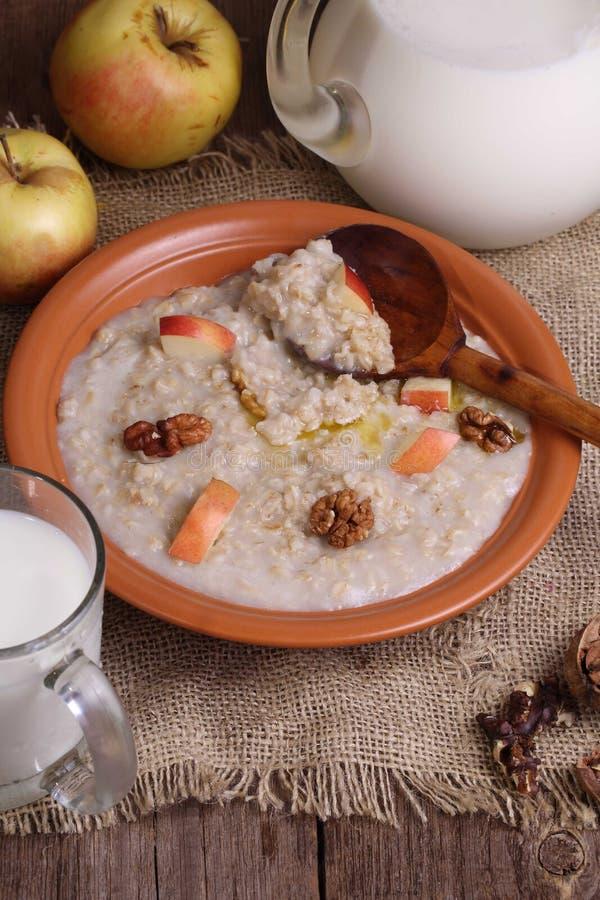 Κουάκερ με το γάλα, τα καρύδια και τα μήλα στοκ φωτογραφίες