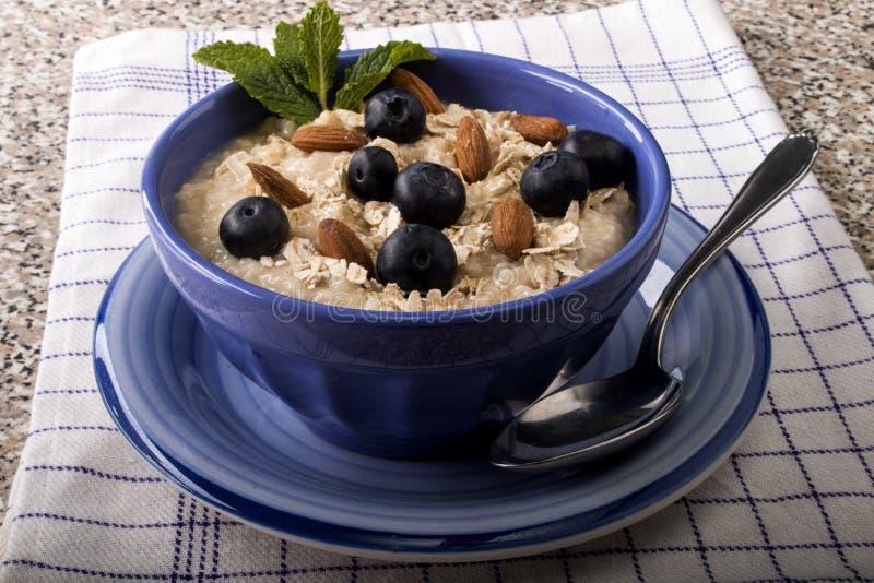 Κουάκερ που γίνεται με παραδοσιακό ιρλανδικό oatmeal σε ένα μπλε κύπελλο στοκ φωτογραφία με δικαίωμα ελεύθερης χρήσης