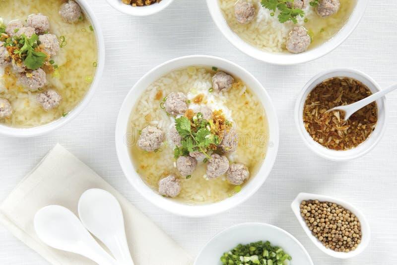 Κουάκερ ρυζιού με τις μπριζόλες χοιρινού κρέατος και καρύκευμα στα άσπρα κύπελλα στον άσπρο πίνακα τοπ άποψης, κινεζικά τρόφιμα στοκ φωτογραφίες