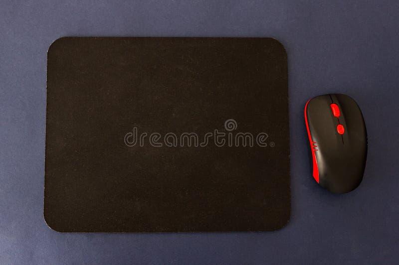 Κουβέρτα υπολογιστών και ποντίκι σε ένα μπλε υπόβαθρο, μαύρο χαλί υπολογιστών στοκ φωτογραφία με δικαίωμα ελεύθερης χρήσης