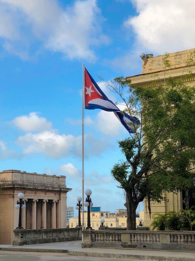 Κουβανική σημαία που κυματίζει στον αέρα και το παλαιό πανεπιστήμιο στοκ εικόνες