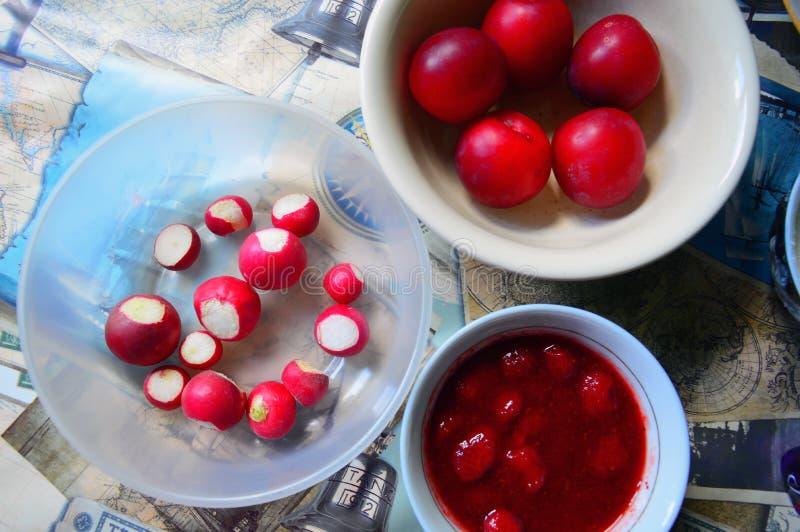 Κουζίνα Τα στρογγυλά πιάτα με τα κόκκινα προϊόντα είναι στον πίνακα Δαμάσκηνα, ραδίκια και μαρμελάδα φραουλών στοκ φωτογραφίες με δικαίωμα ελεύθερης χρήσης