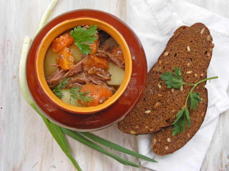 Κουζίνα της λευκορωσικής, ρωσικής παραδοσιακής κουζίνας: Μαγειρευμένο κουνέλι με Goulash λαχανικών στο δοχείο χαλκού στην ξύλινη  στοκ εικόνες