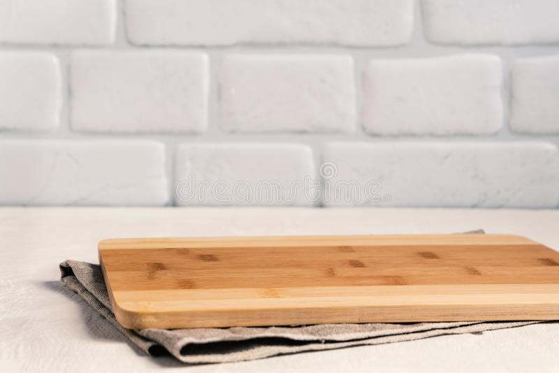 Κουζίνα υποβάθρου με τον τέμνοντα πίνακα στον άσπρο ξύλινο πίνακα, με το τραπεζομάντιλο λινού στο κλίμα ένας τουβλότοιχος στοκ εικόνες με δικαίωμα ελεύθερης χρήσης