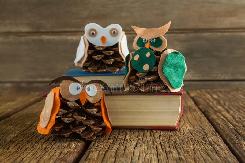Κουκουβάγια που διακοσμείται με τον κώνο πεύκων και το σωρό βιβλίων στον ξύλινο πίνακα στοκ εικόνες με δικαίωμα ελεύθερης χρήσης