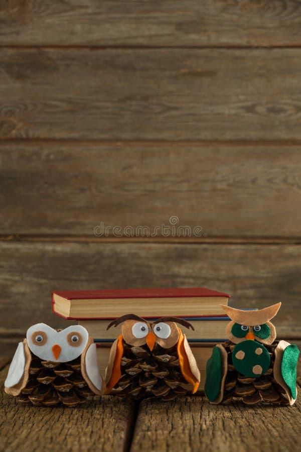 Κουκουβάγια που διακοσμείται με τον κώνο πεύκων και το σωρό βιβλίων στον ξύλινο πίνακα στοκ φωτογραφία
