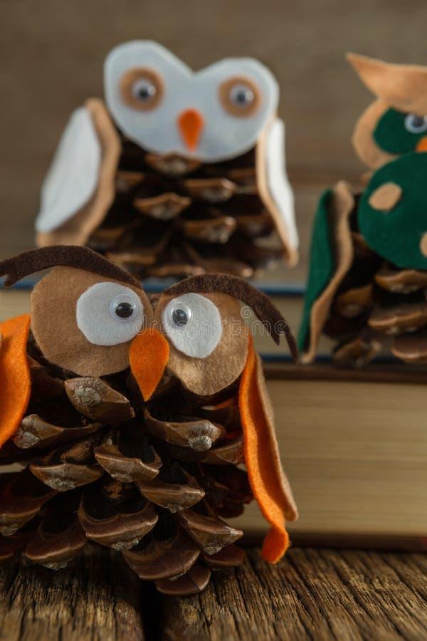 Κουκουβάγια που διακοσμείται με τον κώνο πεύκων και το σωρό βιβλίων στον ξύλινο πίνακα στοκ εικόνες
