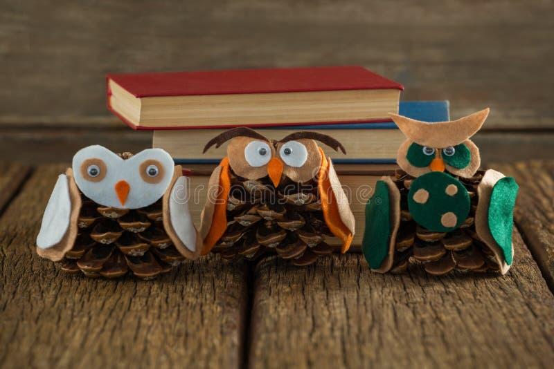 Κουκουβάγια που διακοσμείται με τον κώνο πεύκων και το σωρό βιβλίων στον ξύλινο πίνακα στοκ εικόνα με δικαίωμα ελεύθερης χρήσης