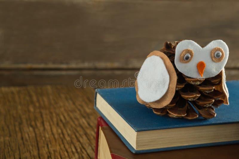 Κουκουβάγια που διακοσμείται με τον κώνο πεύκων και το σωρό βιβλίων στον ξύλινο πίνακα στοκ φωτογραφία με δικαίωμα ελεύθερης χρήσης