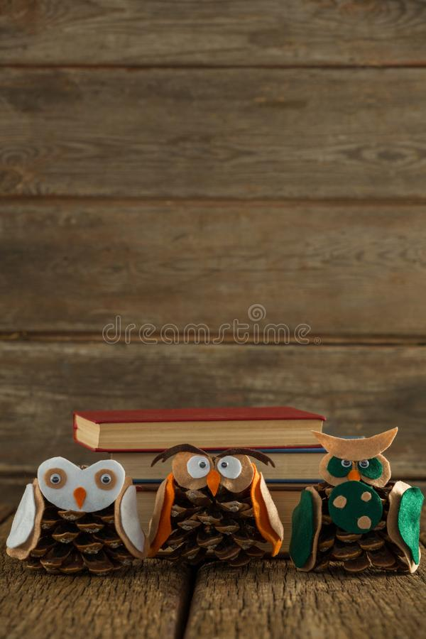 Κουκουβάγια που διακοσμείται με τον κώνο πεύκων και το σωρό βιβλίων στον ξύλινο πίνακα στοκ εικόνα