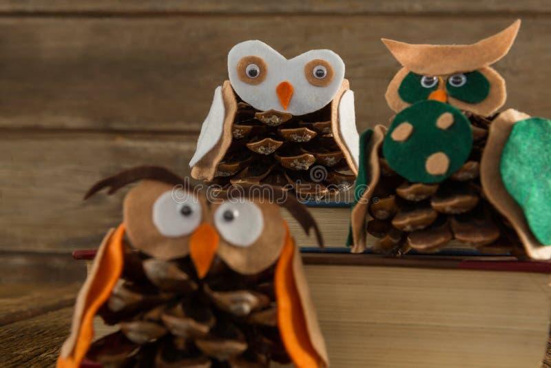 Κουκουβάγια που διακοσμείται με τον κώνο πεύκων και το σωρό βιβλίων στον ξύλινο πίνακα στοκ φωτογραφίες