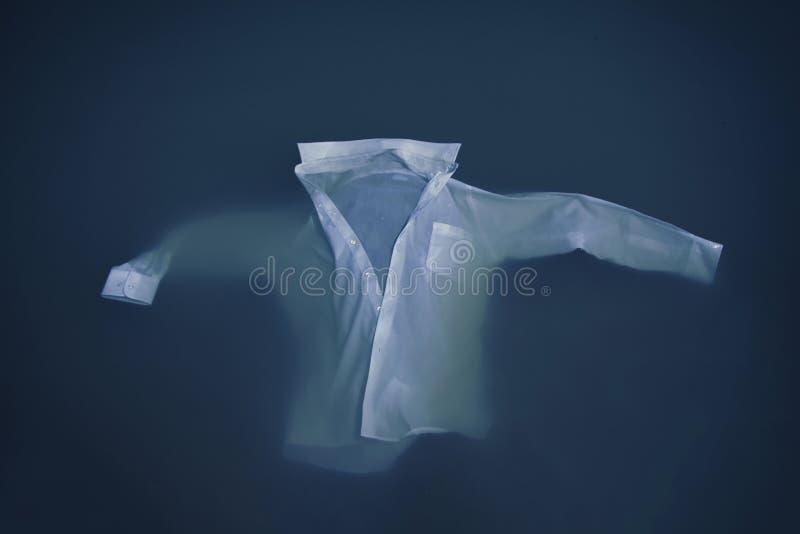 Κουμπί ατόμων επάνω στο πουκάμισο που επιπλέει ή που βυθίζει στο νερό στοκ φωτογραφία με δικαίωμα ελεύθερης χρήσης