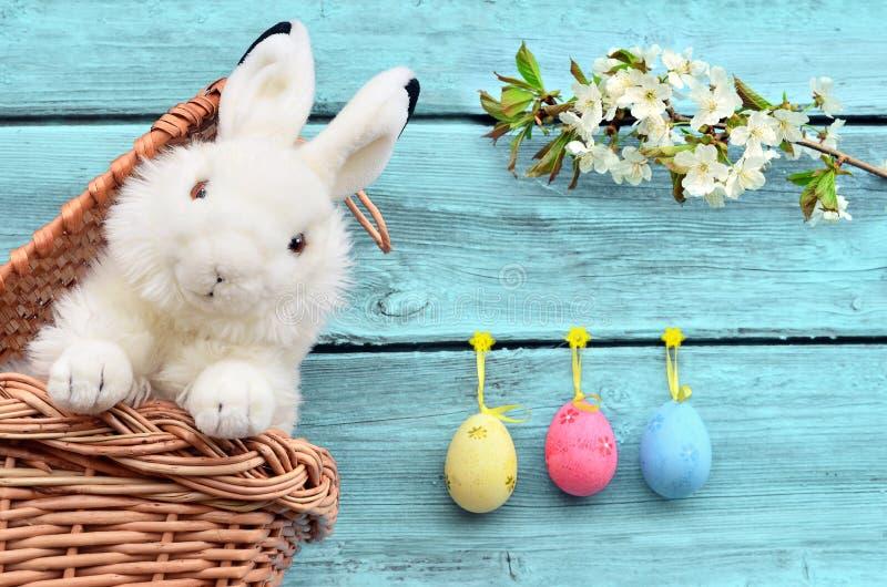 Κουνέλια στο καλάθι με τα αυγά Πάσχας και το λουλούδι στοκ φωτογραφία με δικαίωμα ελεύθερης χρήσης