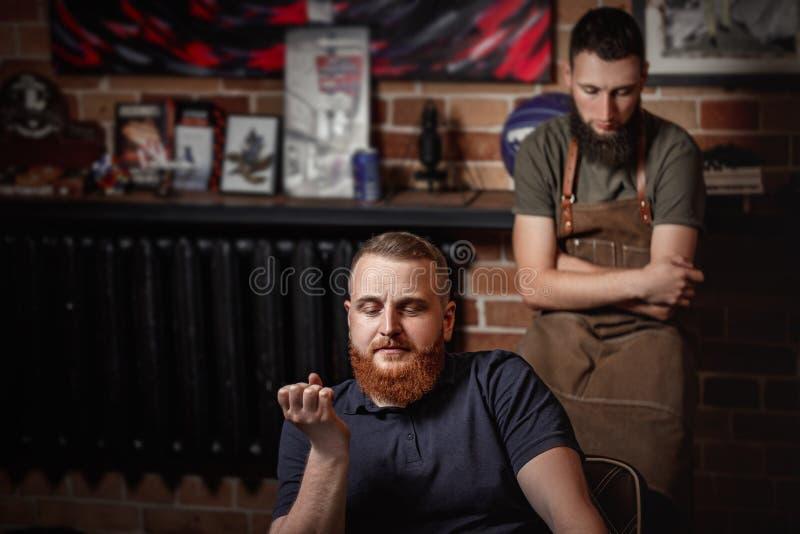 Κουρέας και γενειοφόρο άτομο στο κατάστημα κουρέων στοκ εικόνες