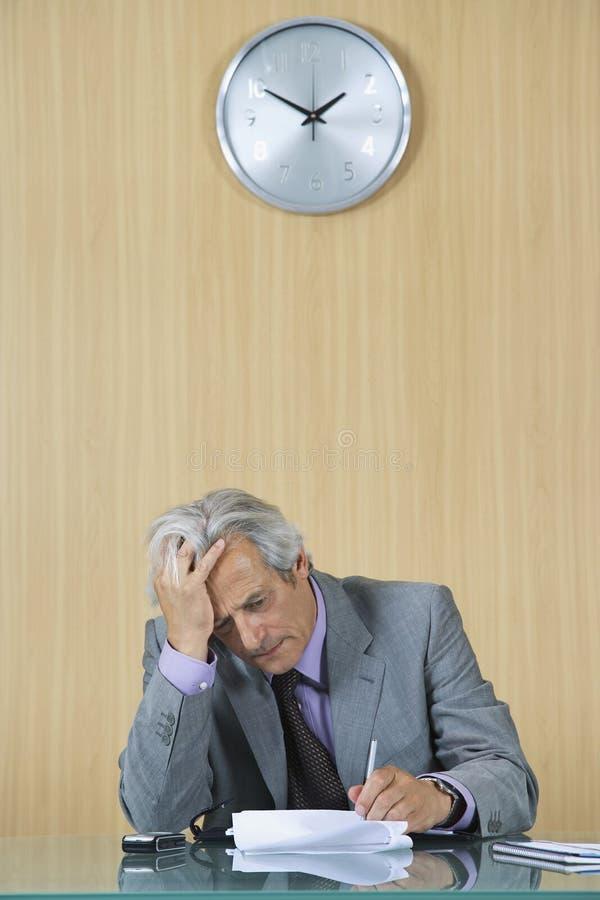 Κουρασμένα έγγραφα ανάγνωσης επιχειρηματιών στην αρχή στοκ εικόνες