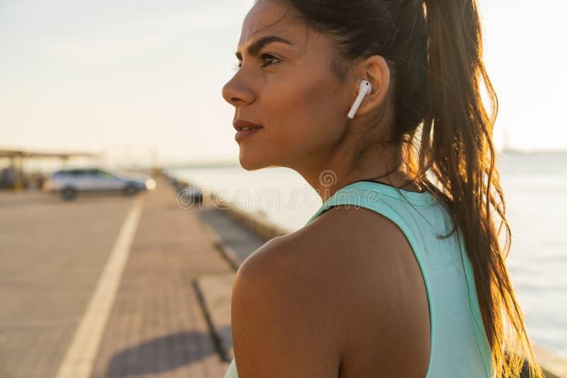Κουρασμένη γυναίκα ικανότητας που ιδρώνει παίρνοντας ένα σπάσιμο που ακούει τη μουσική στο τηλέφωνο μετά από τη δύσκολη κατάρτιση στοκ εικόνες