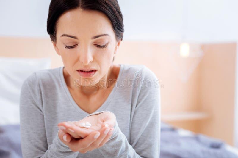 Κουρασμένη γυναίκα που ανοίγει το στόμα της πρίν παίρνει τα χάπια στοκ φωτογραφία