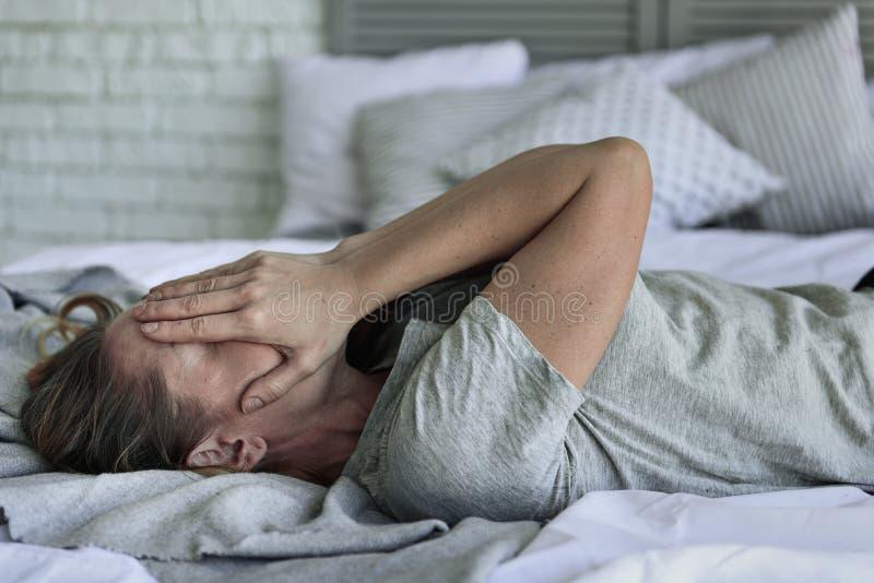 Κουρασμένη γυναίκα που βρίσκεται στο πλαίσιο κρεβατιού στοκ εικόνες με δικαίωμα ελεύθερης χρήσης