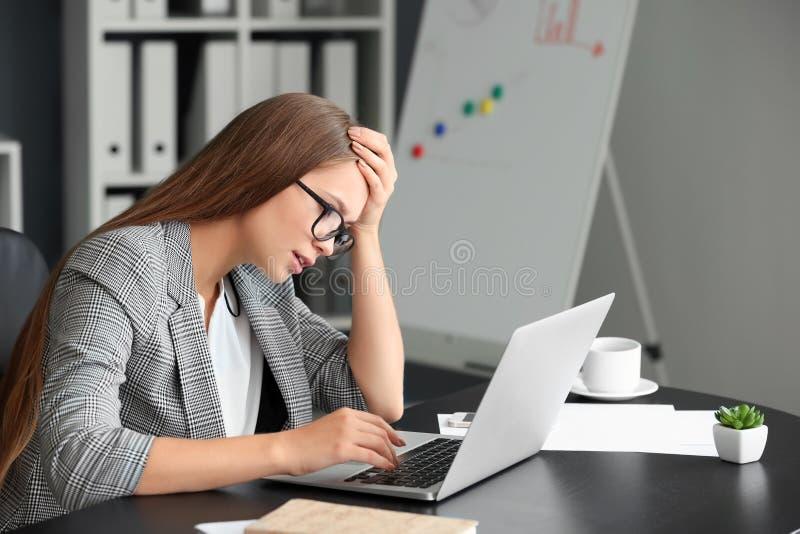 Κουρασμένη γυναίκα που εργάζεται στο lap-top στην αρχή στοκ φωτογραφία με δικαίωμα ελεύθερης χρήσης