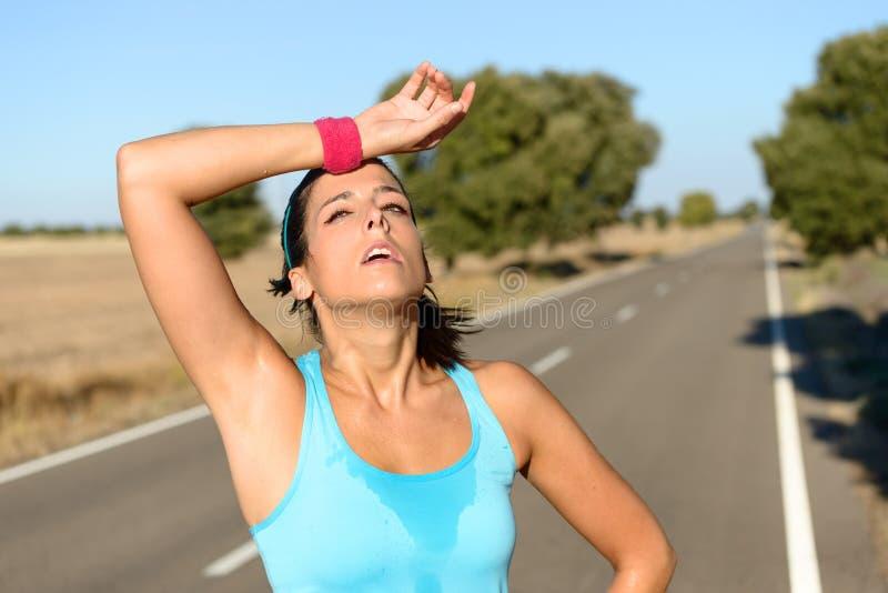 Κουρασμένη γυναίκα που ιδρώνει μετά από να τρέξει στοκ εικόνες με δικαίωμα ελεύθερης χρήσης