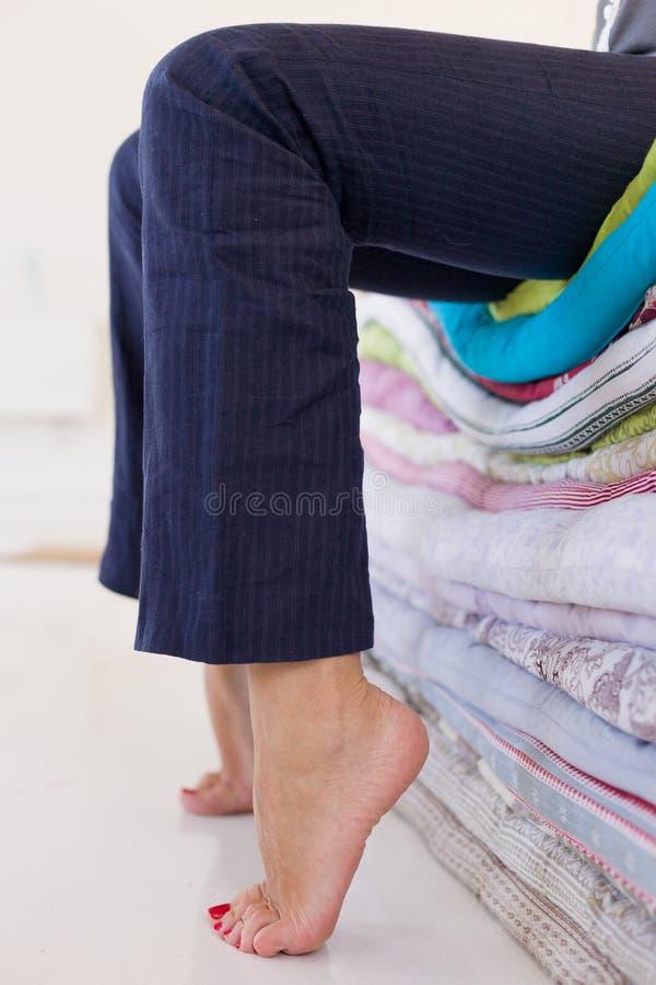 Κουρασμένη γυναίκα στο μπλε παντελόνι που κάθεται στο σωρό των στρωμάτων που χαλαρώνουν μετά από την εργάσιμη ημέρα Γυμνά πόδια ε στοκ φωτογραφία με δικαίωμα ελεύθερης χρήσης