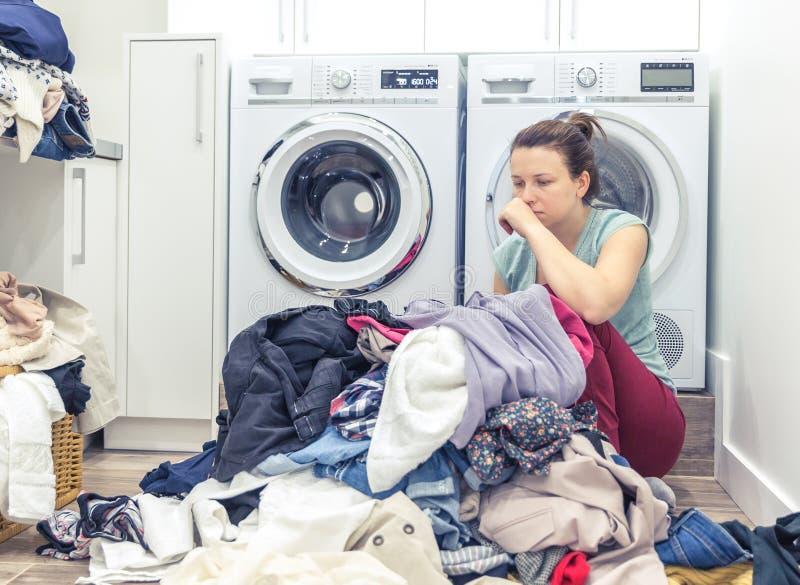 Κουρασμένη δυστυχισμένη νοικοκυρά γυναικών σε ένα δωμάτιο πλυντηρίων κοντά στο πλυντήριο στοκ εικόνες
