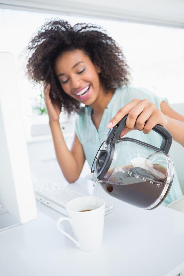 Κουρασμένη επιχειρηματίας που χύνει ένα φλιτζάνι του καφέ στο γραφείο στοκ εικόνα με δικαίωμα ελεύθερης χρήσης