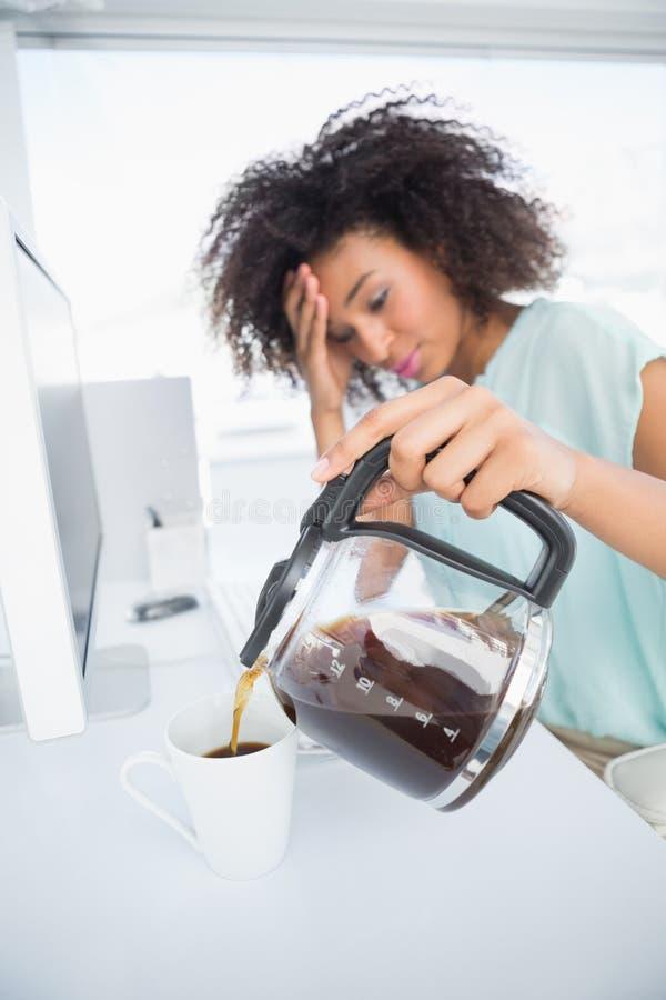 Κουρασμένη επιχειρηματίας που χύνει ένα φλιτζάνι του καφέ στο γραφείο στοκ φωτογραφία με δικαίωμα ελεύθερης χρήσης