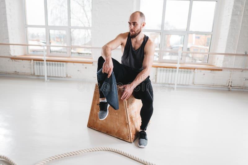 Κουρασμένη μυϊκή συνεδρίαση ατόμων στο κιβώτιο στη γυμναστική crossfit στοκ φωτογραφίες