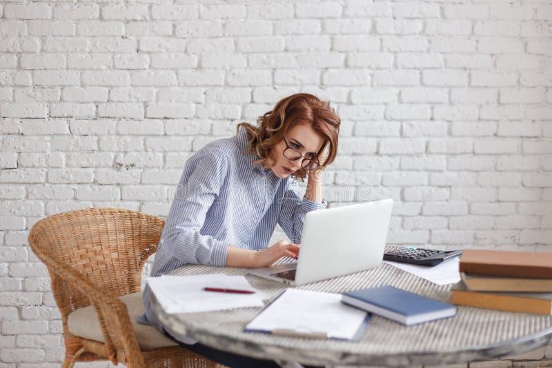 Κουρασμένη νέα γυναίκα στον υπολογιστή εργασία μερών στοκ φωτογραφίες