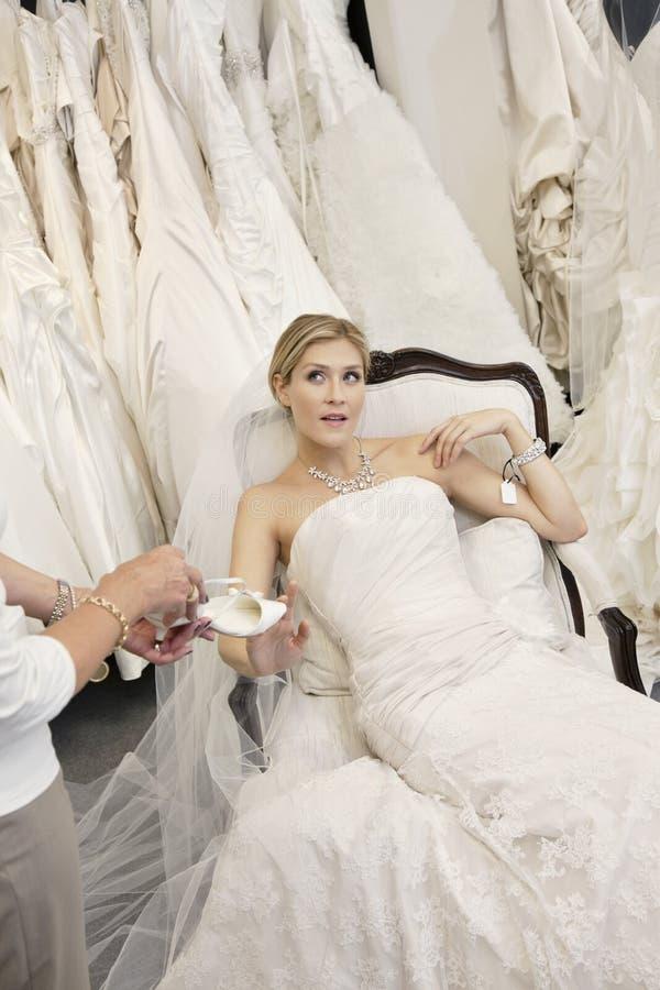 Κουρασμένη νέα νύφη στη συνεδρίαση γαμήλιων φορεμάτων ενώ μητέρα που παρουσιάζει υποδήματα στοκ φωτογραφία με δικαίωμα ελεύθερης χρήσης