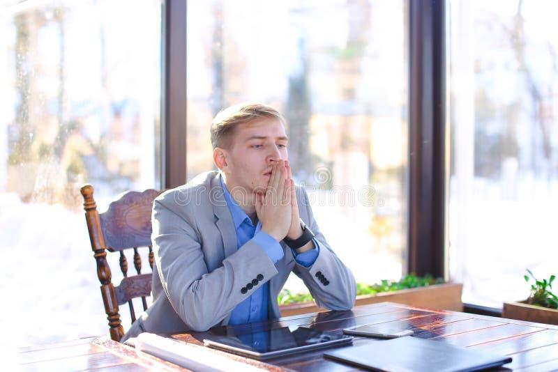 Κουρασμένη νέα συνεδρίαση καθηγητή στον καφέ με το έγγραφο ρόλων, smartphon στοκ φωτογραφία με δικαίωμα ελεύθερης χρήσης