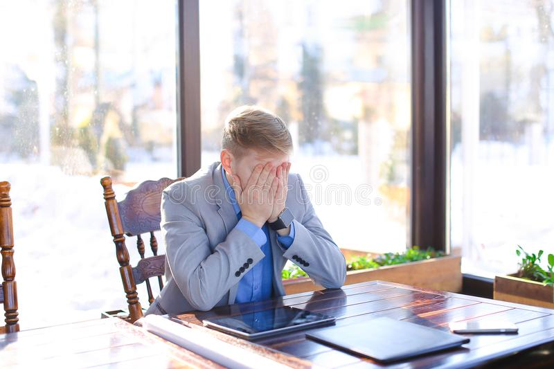 Κουρασμένη νέα συνεδρίαση καθηγητή στον καφέ με το έγγραφο ρόλων, smartphon στοκ εικόνες με δικαίωμα ελεύθερης χρήσης